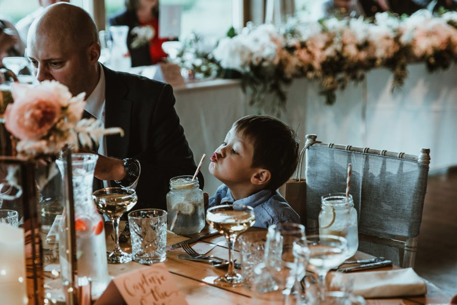 small boy trying to drink from a straw at wedding.