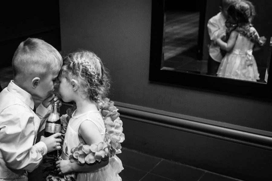 two children share a diet coke at a wedding